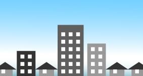 立ち並ぶビルと家と青い空