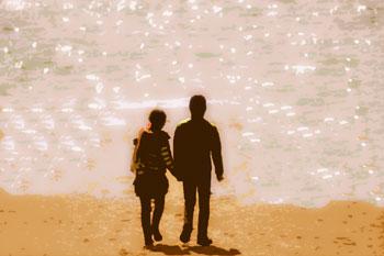 日が沈む時刻にキラキラ光るビーチでたたずむと恋人たち