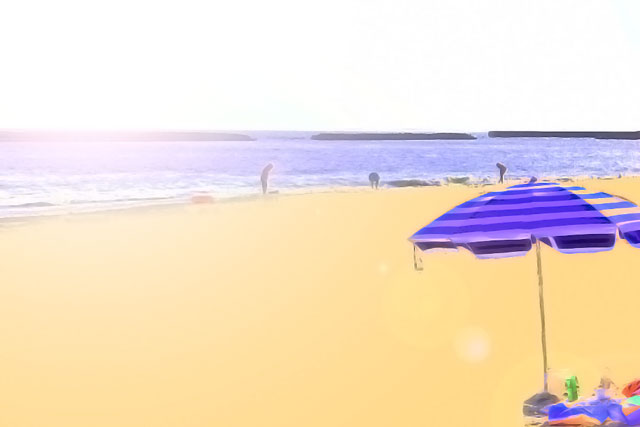 ビーチパラソルと海辺で遊び人たち