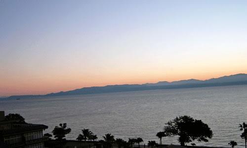 夕暮れと海と山とヤシの木の風景の拡大写真