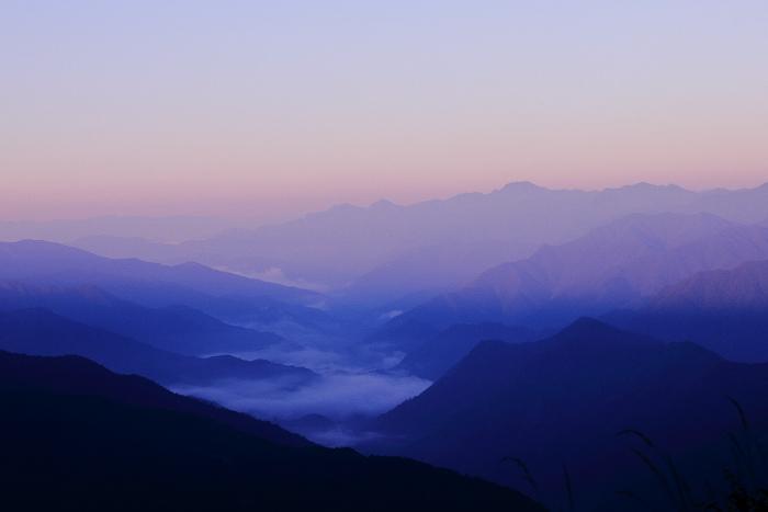 大きいサイズの重なり合う山々を朝日が照り付ける