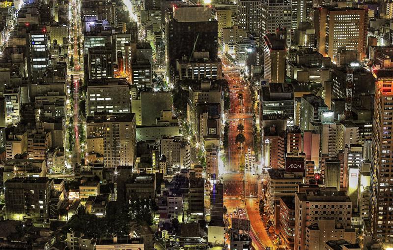 大きいサイズのオフィスビルの明かりとテールランプの軌跡