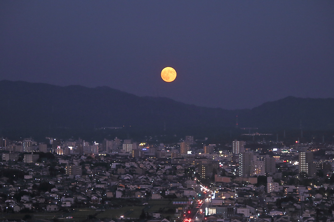 大きいサイズの都市の夜景とスーパームーン